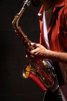 Seitenansicht des männlichen musikers, der saxophon spielt