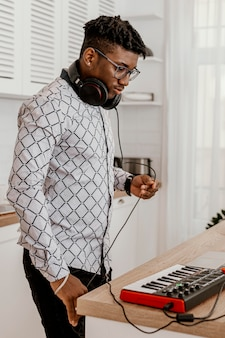 Seitenansicht des männlichen musikers mit kopfhörern und elektrischer tastatur
