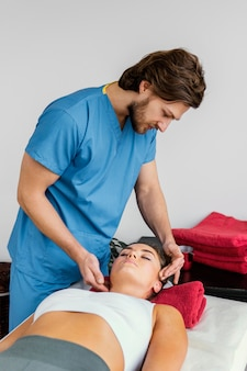 Seitenansicht des männlichen osteopathischen therapeuten, der die halswirbelsäule des weiblichen patienten prüft