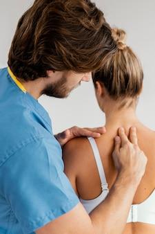 Seitenansicht des männlichen osteopathischen therapeuten, der die wirbelsäule der patientin prüft