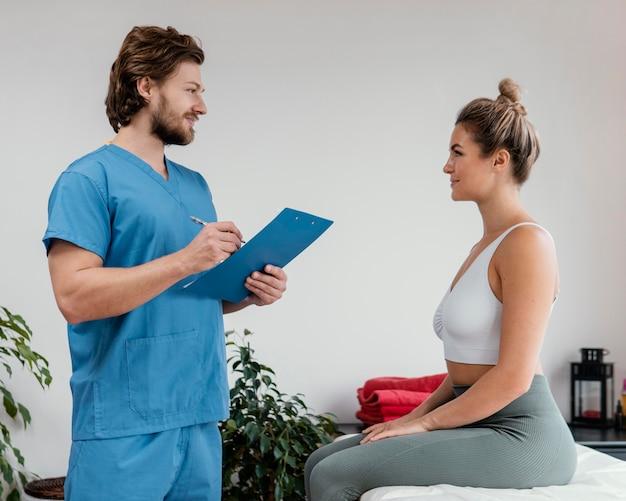 Seitenansicht des männlichen osteopathischen therapeuten mit der weiblichen patientenunterzeichnungs-zwischenablage an der klinik