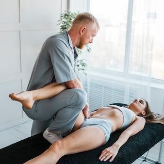 Seitenansicht des männlichen physiotherapeuten, der übungen am weiblichen patienten durchführt