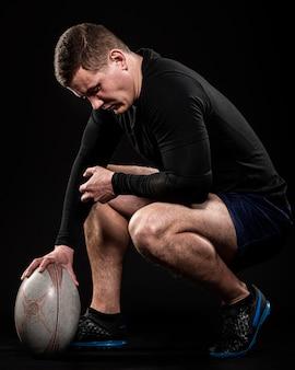 Seitenansicht des männlichen rugbyspielers, der ball mit einer hand hält
