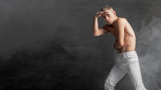 Seitenansicht des männlichen tänzers aufwerfend in den jeans mit rauch- und kopienraum