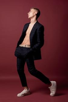 Seitenansicht des männlichen tänzers aufwerfend in der klage ohne hemd und turnschuhe