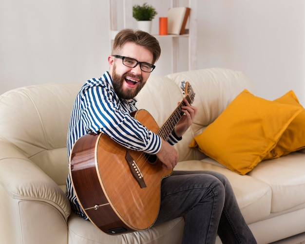 Seitenansicht des mannes auf dem sofa, das gitarre spielt