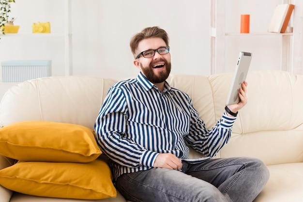 Seitenansicht des mannes auf sofa mit tablette