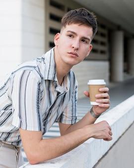Seitenansicht des mannes, der draußen mit kaffee aufwirft