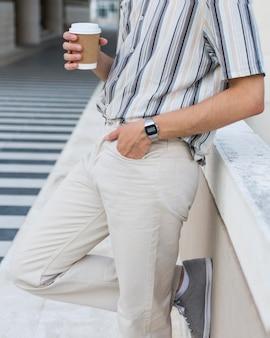 Seitenansicht des mannes, der draußen mit kaffee entspannt