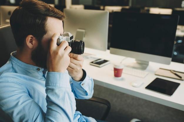 Seitenansicht des mannes, der foto nimmt, das am schreibtisch im büro mit computertablett und tasse sitzt
