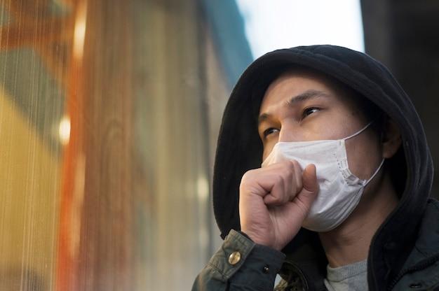 Seitenansicht des mannes, der hustet, während er eine medizinische maske trägt