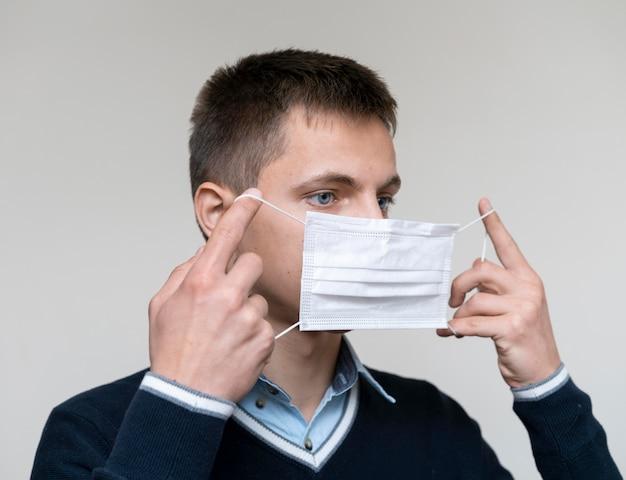 Seitenansicht des mannes, der medizinische maske aufsetzt