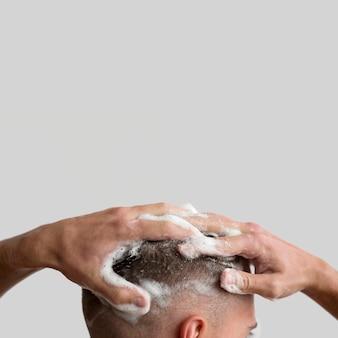 Seitenansicht des mannes, der seine haare mit shampoo wäscht