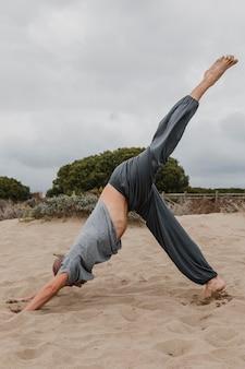 Seitenansicht des mannes, der yoga draußen praktiziert