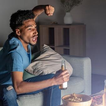 Seitenansicht des mannes, der zu hause am fernseher mit bier und snacks jubelt