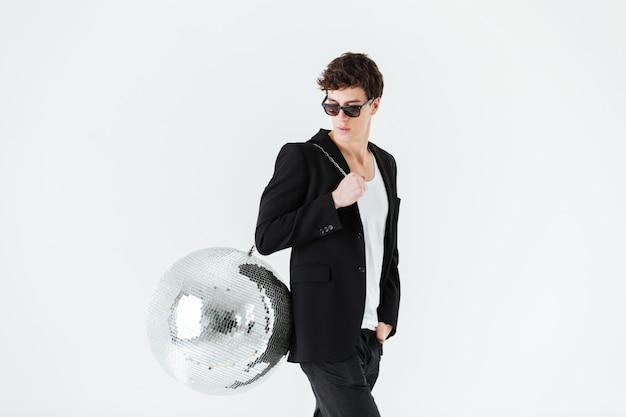 Seitenansicht des mannes im anzug, der discokugel trägt