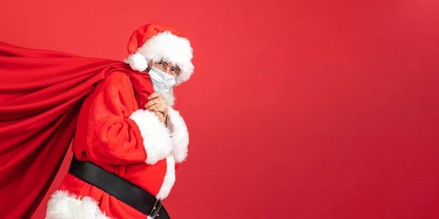 Seitenansicht des mannes im weihnachtsmannkostüm, das geschenktüte trägt