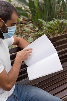 Seitenansicht des mannes mit der medizinischen maske, die buch auf bank im freien liest