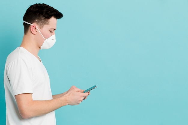 Seitenansicht des mannes mit der medizinischen maske, die coronavirus auf smartphone nachschaut