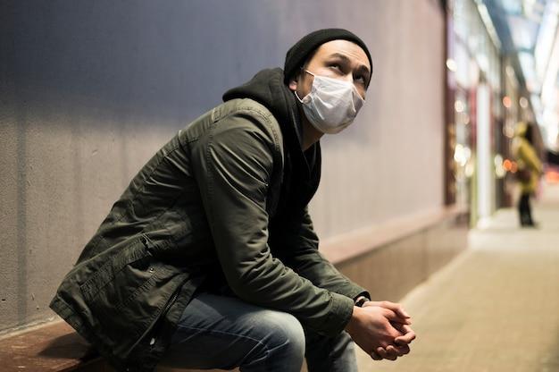 Seitenansicht des mannes mit der medizinischen maske, die draußen sitzt