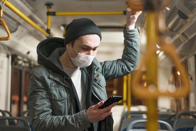 Seitenansicht des mannes mit der medizinischen maske im bus unter verwendung des smartphones