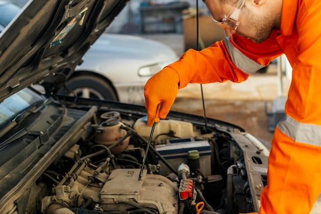 Seitenansicht des mechanikers in uniform mit schutzbrille