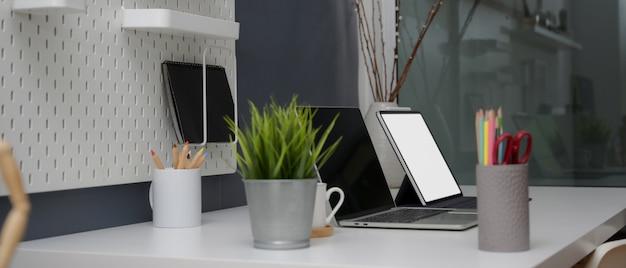 Seitenansicht des minimalen schreibtischs mit nachgebauten digitalen geräten, verbrauchsmaterialien und dekorationen