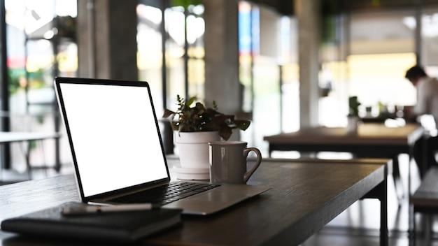 Seitenansicht des modernen arbeitsbereichs mit einem computerlaptop des leeren bildschirms. leerer bildschirm für die montage der grafikanzeige.