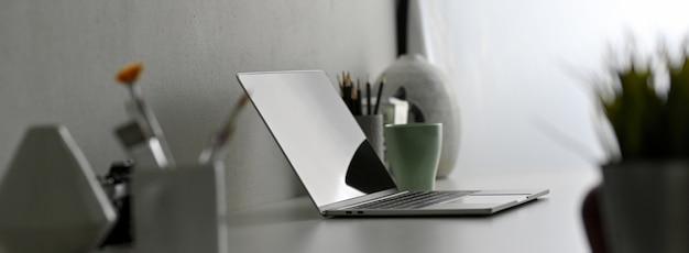 Seitenansicht des modernen schreibtischs mit laptop, malwerkzeugen und dekorationen