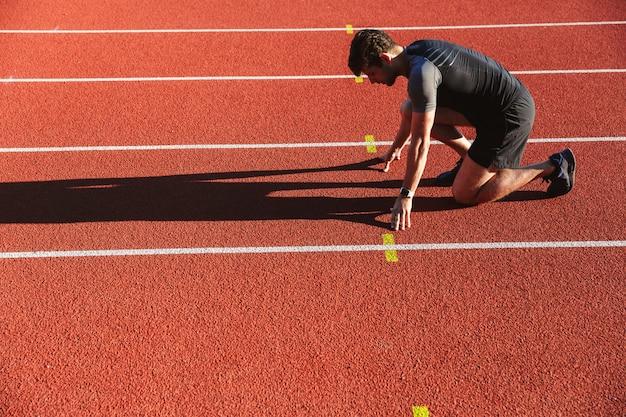 Seitenansicht des motivierten jungen sportlers, der sich bereit macht