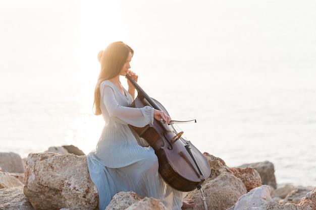Seitenansicht des musikers, der cello auf felsen durch das meer spielt