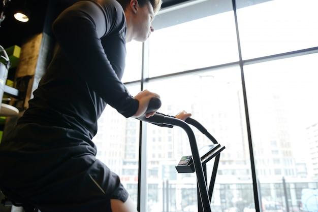 Seitenansicht des muskulösen mannes unter verwendung des sich drehenden fahrrads