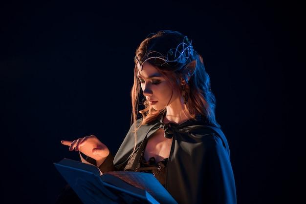 Seitenansicht des mystischen weiblichen schönen elfen, der magisches buch in der dunkelheit liest.