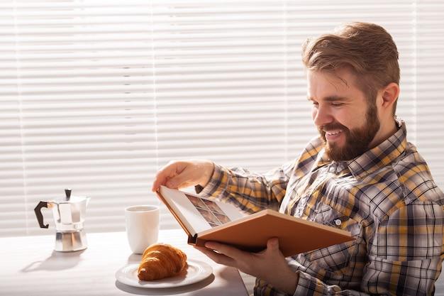 Seitenansicht des nachdenklichen jungen bärtigen hipster-mannes, der buch liest und mit croissant zu abend isst