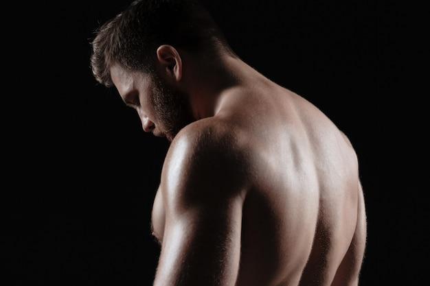 Seitenansicht des nackten muskulösen mannes. isolierter dunkler hintergrund