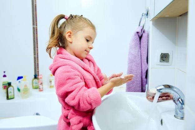 Seitenansicht des netten kleinen mädchens mit pferdeschwanz im rosa bademantel, der ihre hände wäscht.