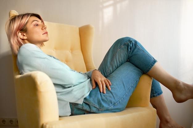 Seitenansicht des niedlichen studentenmädchens, das barfuß im bequemen sessel liegt, der sich entspannt.