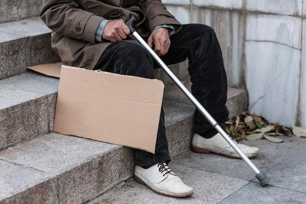 Seitenansicht des obdachlosen auf der treppe mit zuckerrohr und leerem schild