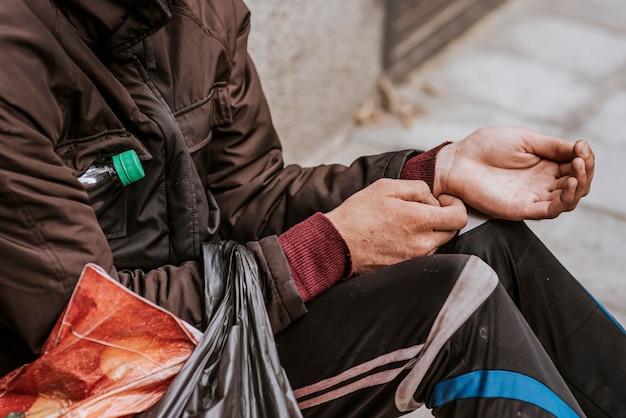 Seitenansicht des obdachlosen, der hände für hilfe heraushält