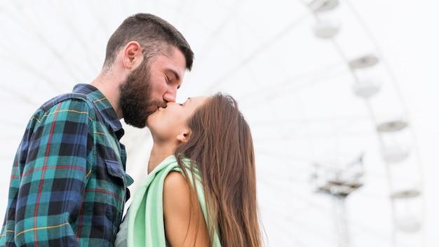Seitenansicht des paares, das draußen küsst