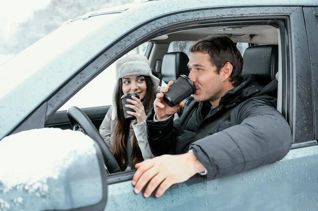 Seitenansicht des paares, das ein warmes getränk im auto während eines roadtrips genießt