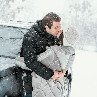 Seitenansicht des paares, das im schnee küsst, während auf einem straßenausflug