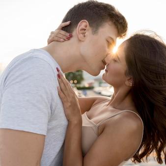 Seitenansicht des paares, das mit der sonne küsst, die zwischen ihnen späht