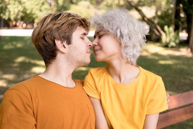 Seitenansicht des paares, das sich für einen kuss im park lehnt
