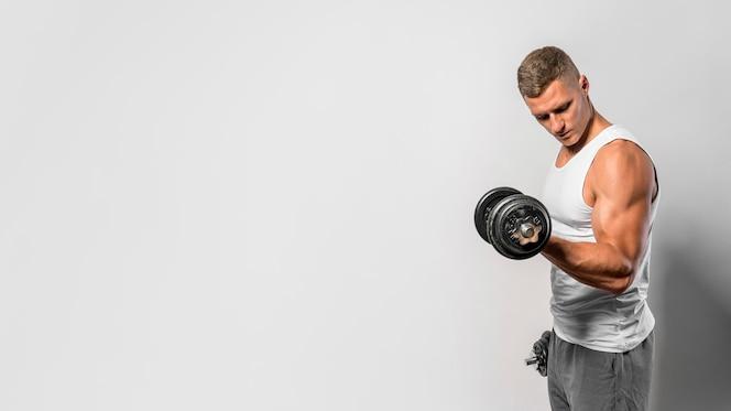 Seitenansicht des passenden mannes mit tanktop unter verwendung von gewichten