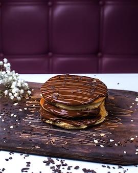 Seitenansicht des pfannkuchens mit schokolade auf einem holzbrett