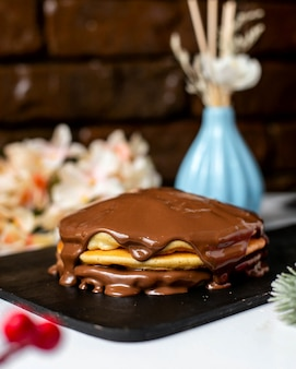 Seitenansicht des pfannkuchens mit schokoladenbutter auf einem hölzernen schneidebrett