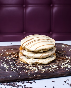 Seitenansicht des pfannkuchens mit weißer schokolade auf einem holzbrett