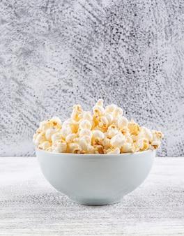 Seitenansicht des popcorns in der schüssel auf weißem holztisch vertikal