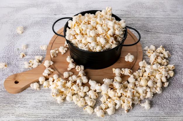 Seitenansicht des popcorns in der schwarzen pfanne und im hölzernen schneidebrett auf der weißen horizontalen
